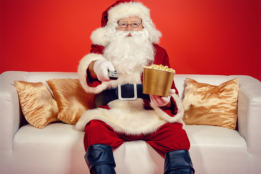 Santa watching tv with popcorn